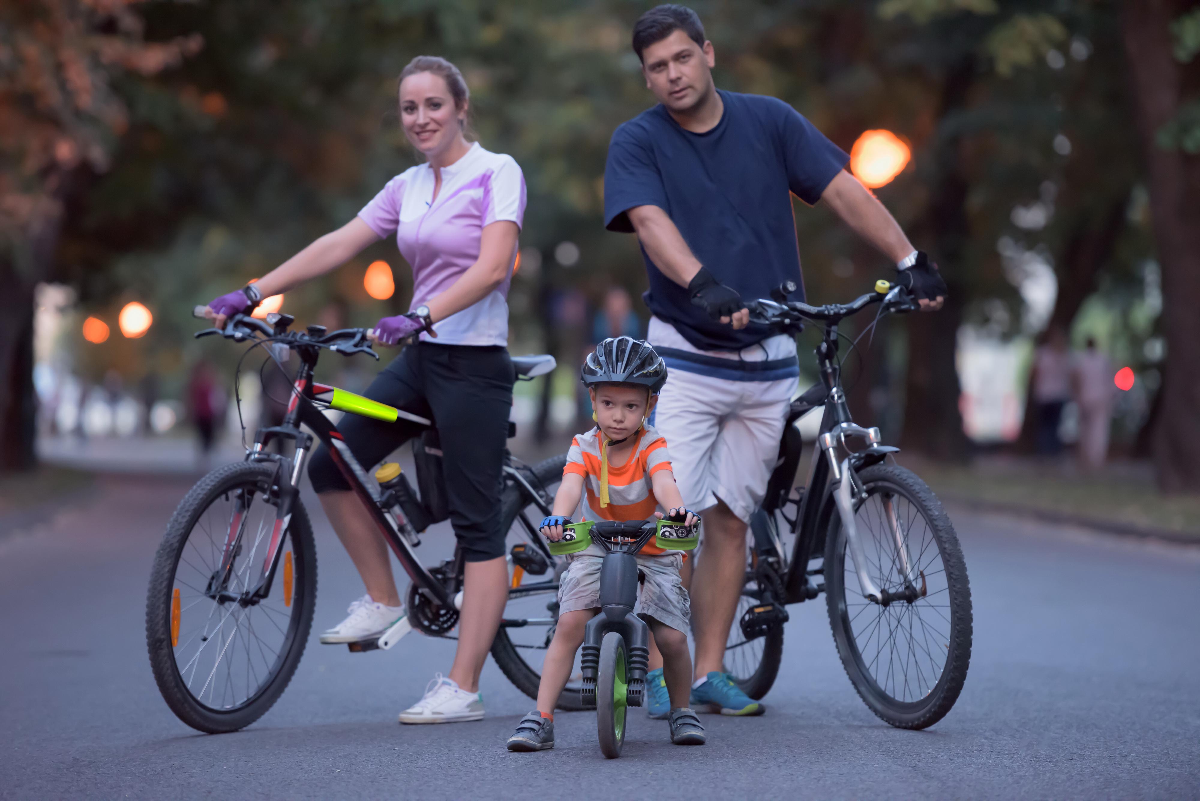 szczęśliwa rodzina na rowerach wyposażonych w odblaski